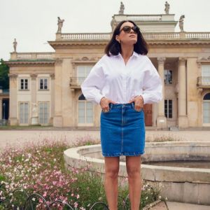 Joanna Horodyńska w białej koszulowej bluzce i jeansowej spódnicy Reserved